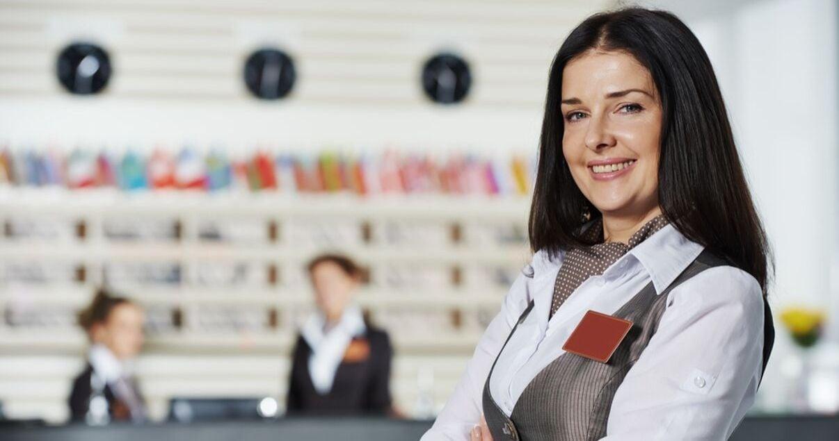 Dos mujeres jovenes adultas recepcionistas de un hotel siendo supervisadas por la especialista en revenue management del alojamiento que mira a camara sonriendo y con actitud hospitalaria