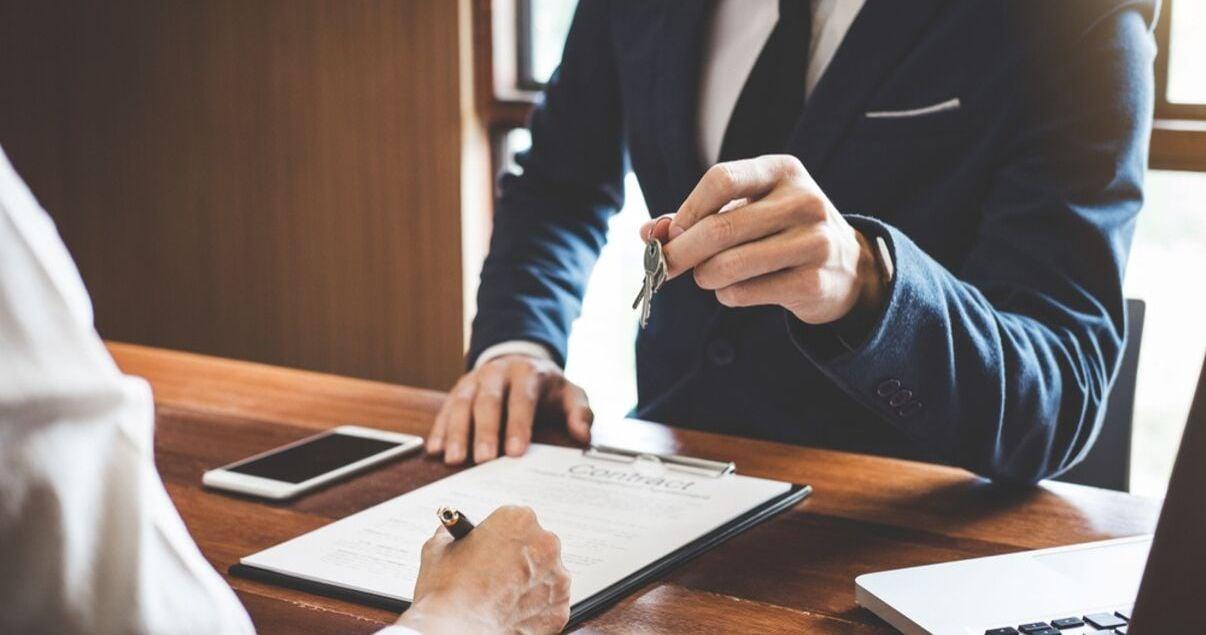 Hombre joven adulto parte del personal de un hotel vestido con traje y corbata azules haciendo el check in a un huesped que arribo producto de una buena gestion de revenue management