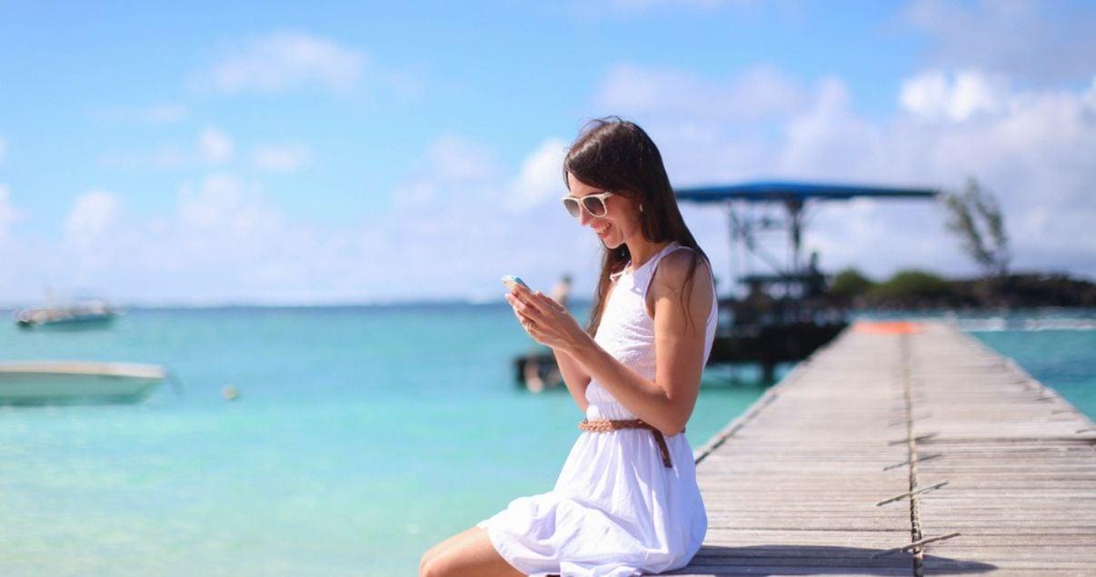Mujer joven adulta de vacaciones en el caribe sentada en el muelle de una gran cadena hotelera con el mar celeste turquesa de fondo y barcos alrededor, chequeando desde su celular las redes sociales para hoteles
