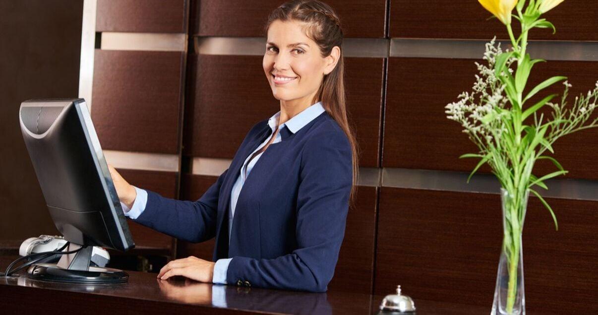 Mujer joven adulta parte del personal de un hotel ubicada en la recepcion frente a un monitor esperando por un huesped para poder hacerle check in
