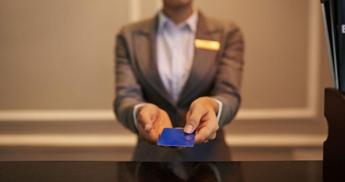 Mujer joven adulta recepcionista de hotel haciendo check in a un huesped haciendole entrega de la tarjeta de acceso a su habitacion producto de una buena gestion de revenue management