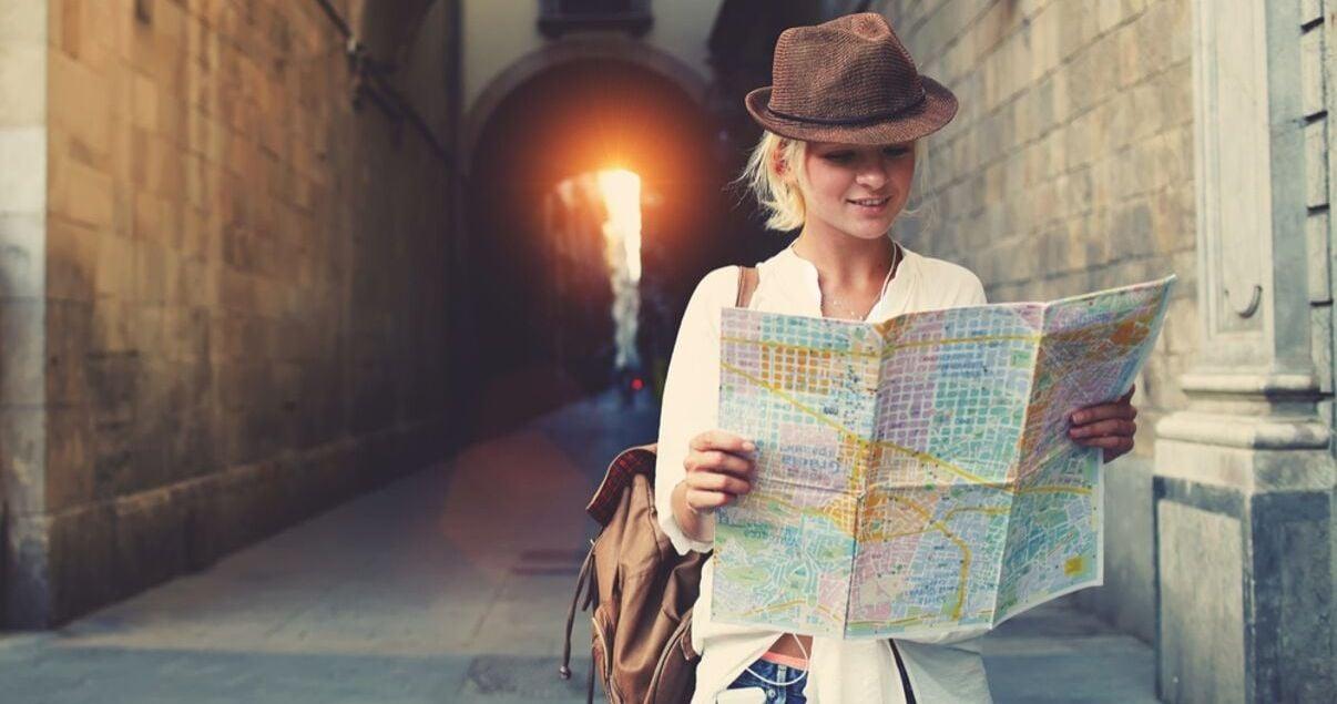 Mujer joven adulta vestida con camisa blanca y sombrero con look aventurero perdida en una ciudad europea mirando el mapa de la ciudad para llegar a su hotel donde se hospeda producto del revenue management