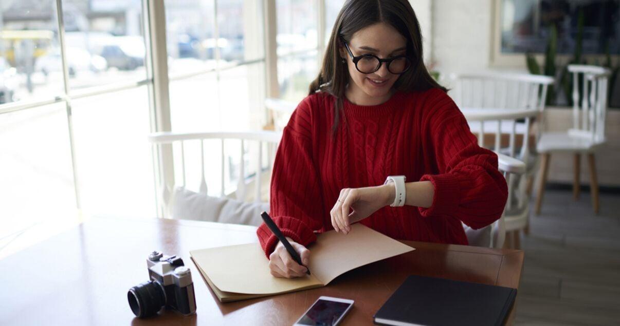 Mujer joven adulta vestida con sueter rojo para asistir a una reunion mientras chequea su reloj en el lobby del hotel en el que se aloja producto del revenue management