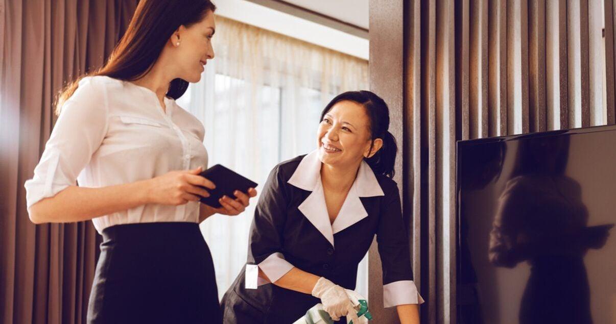 Mujeres jovenes adultas parte del personal de un hotel trabajando en una de las habitaciones del establecimiento preparandola para el proximo huesped