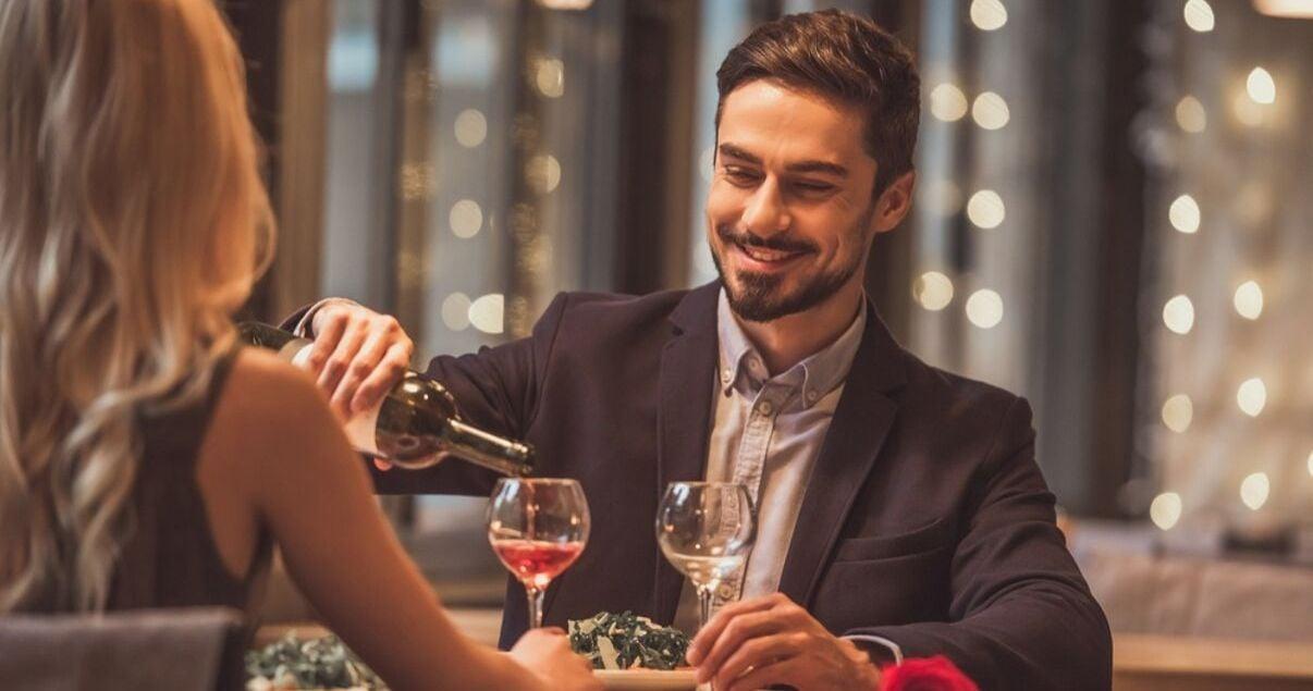 Pareja heterosexual de hombre y mujer jovenes adultos vestidos de gala para una cena romantica en el restaurante de un hotel que les regalo una botella de vino producto de una estrategia de revenue management