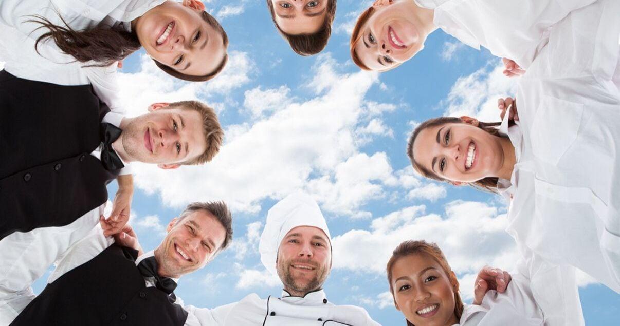 Personal de un hotel de distintas procedencias geograficas todos abrazados y sonrientes con el cielo de fondo