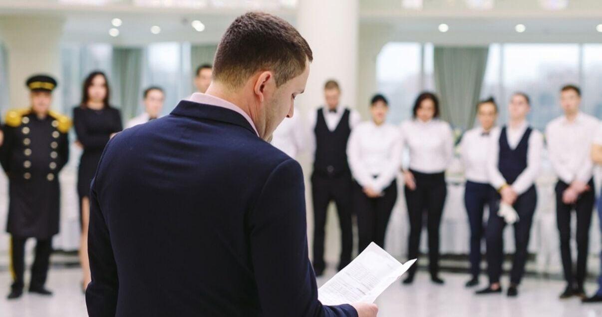 Personal de un hotel en fila vestidos con el uniforme del alojamiento todos en fila mientras asisten a la reunion semanal del gerente de la empresa como parte de la politica de employer branding de la compania