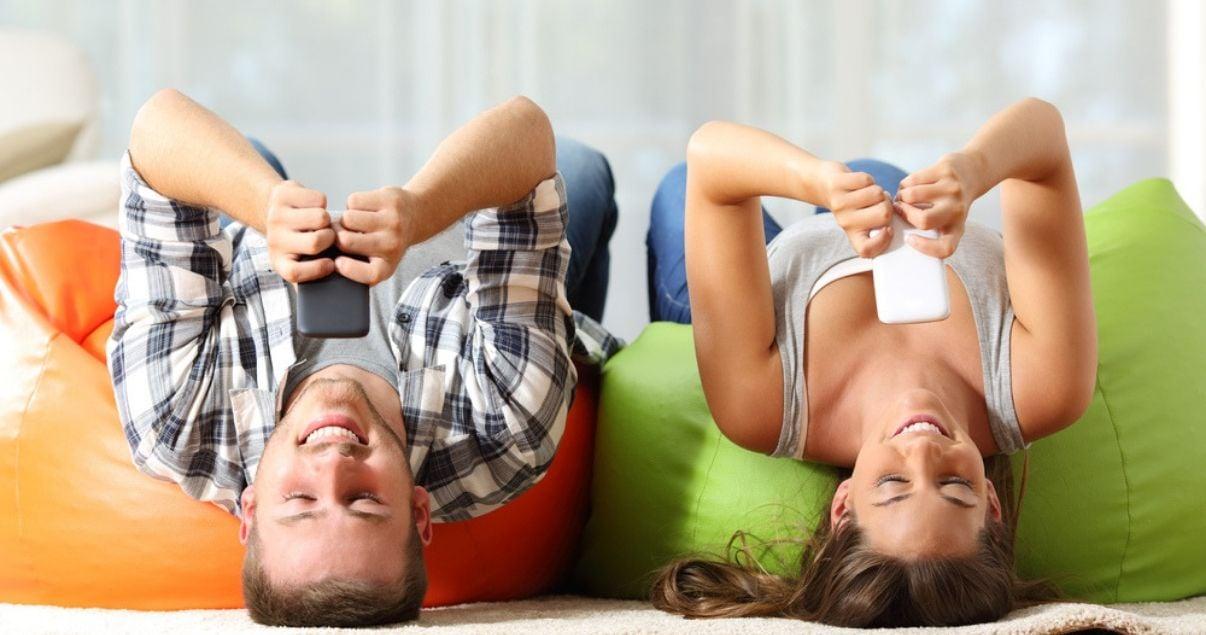 Un hombre joven adulto y una mujer joven adulta de vacaciones tirados en los sillones comodos verde y naranja de su alojamiento, utilizando wifi desde sus telefonos celulares para chequear las redes sociales para hoteles