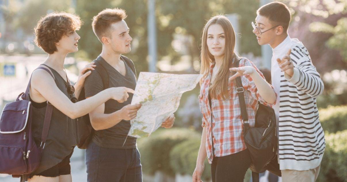 Grupo de jovenes adultos millennials viajeros y huespedes de un hotel perdidos en el centro de una metropolis mientras consultan en un mapa la ubicacion de su destino