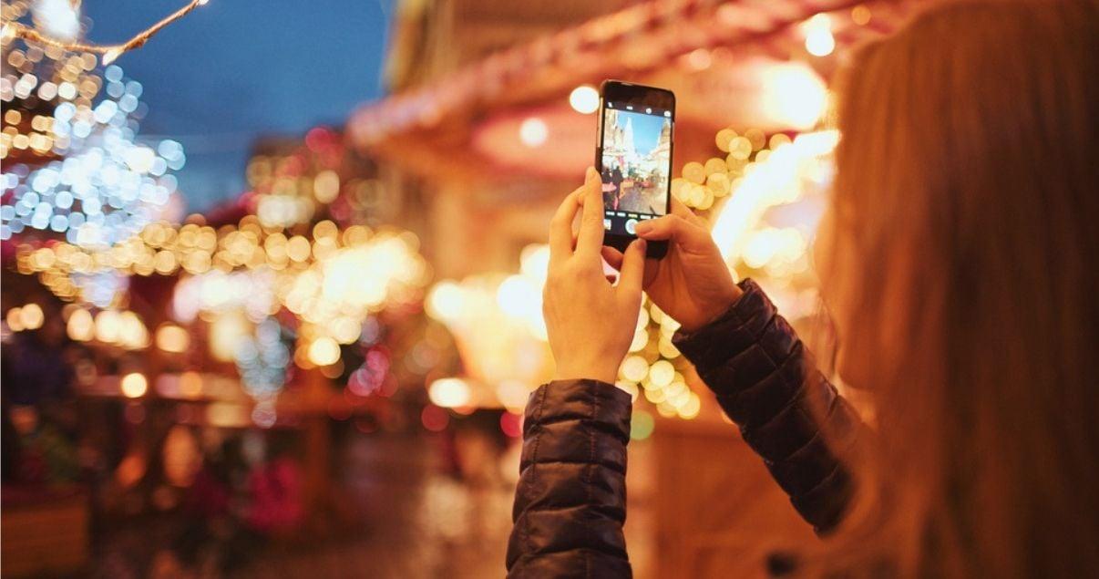 Joven adulta millennial disfruta de Tokyo, Japon mientras saca una foto del paisaje para compartir con sus amigos en redes sociales donde subira el contenido gracias al internet del hotel del que ella es una de los huesped