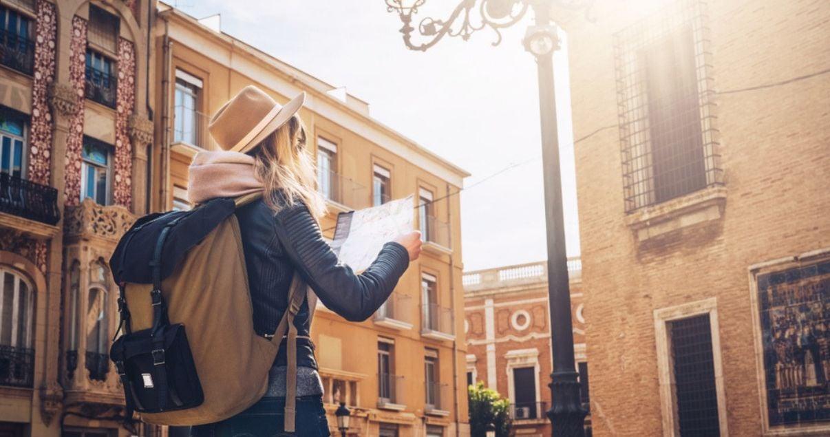 Joven millennial buscando de viaje en Europa buscando en el mapa la ubicacion del hotel del que sera huesped