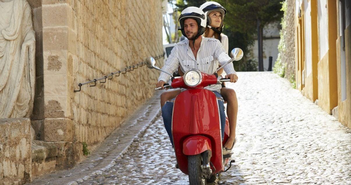Pareja de hombre y mujer huespedes de un hotel en Roma explorando la ciudad en moto como dos aventureros