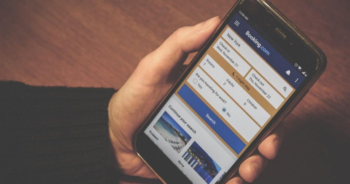 Manos de hombre joven adulto de tez blanca mirando a la pantalla de su telefono celular que tiene el explorador de internet abierto en el sitio web de booking para hacer una gestion de reservas hoteleras