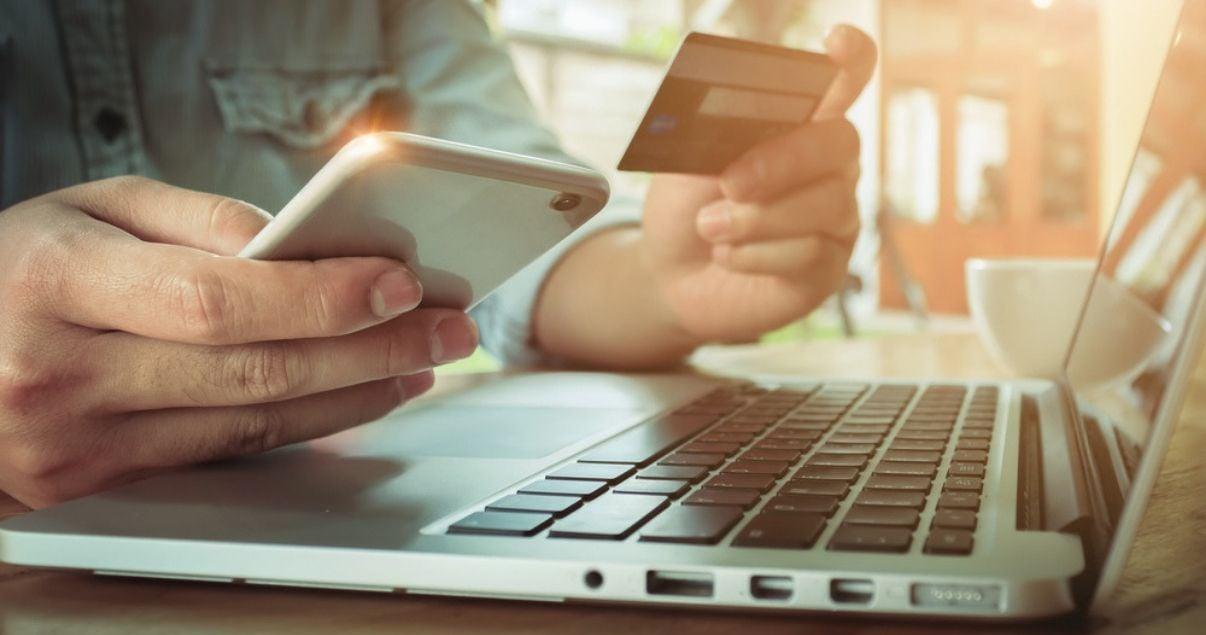 Manos de hombre joven adulto de tez blanca sentado frente a una computadora con su telefono celular y tarjeta de credito porque hara una reserva en un hotel que vende a traves de otas como resultado de su gestion de