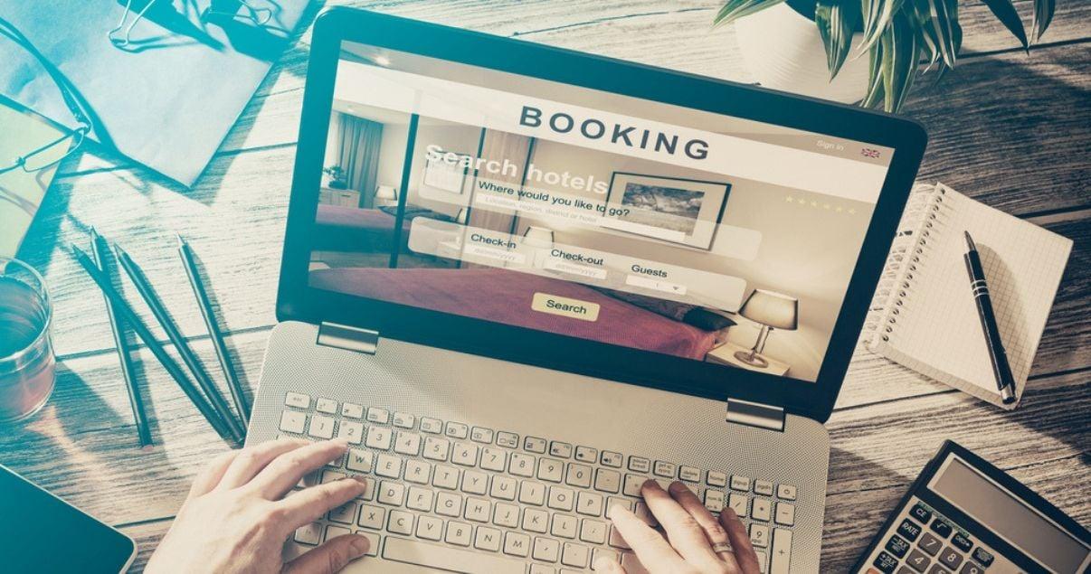 Manos de mujer joven adulta haciendo una reserva en una computadora en una plataforma de reserva de habitaciones en la que su hotel participa como resultado de la gestion de reservas hoteleras de la empresa