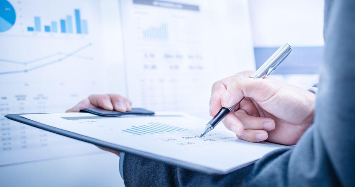 Manos de hombre joven adulto parte del equipo de revenue management de una cadena de hoteles tomando nota de los datos que arroja un reporte de ocupacion del hotel que gestiona