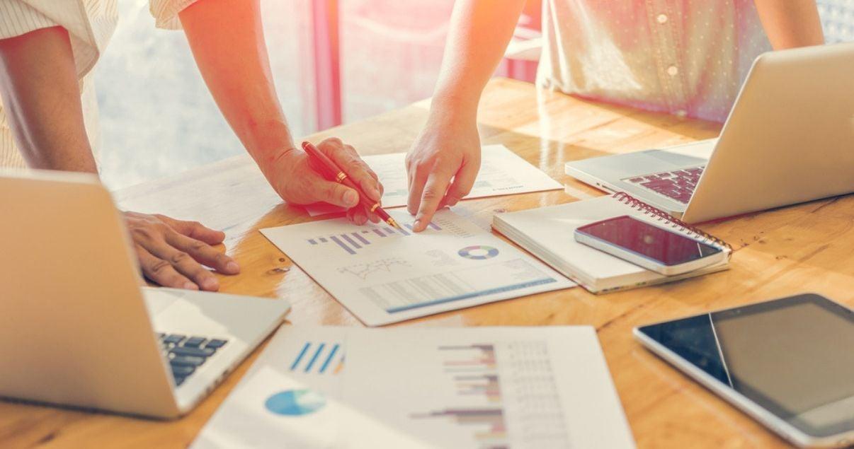 Manos de hombre joven adulto y mujer joven adulta parte del equipo de revenue management de una cadena de hoteles trabajando juntos sobre mesa de madera tomando nota de los datos que arroja un reporte con graficos de