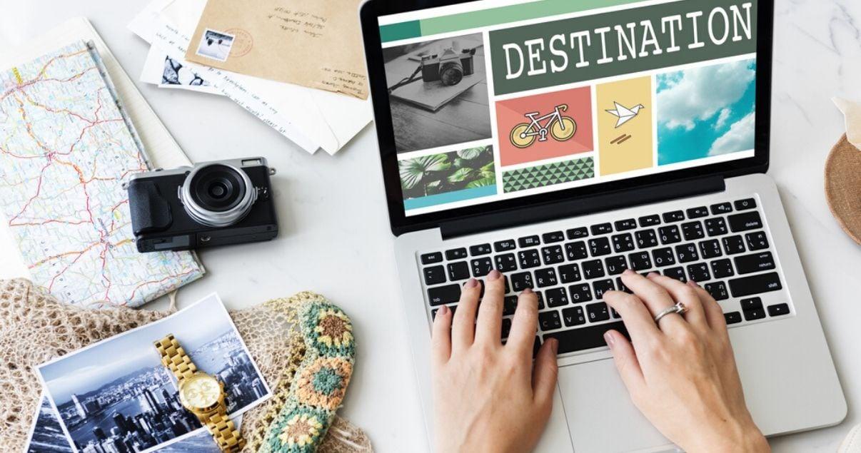 Manos de mujer joven adulta sentada frente a su laptop mientras chequea web para hoteles para reservar sus proximas vacaciones