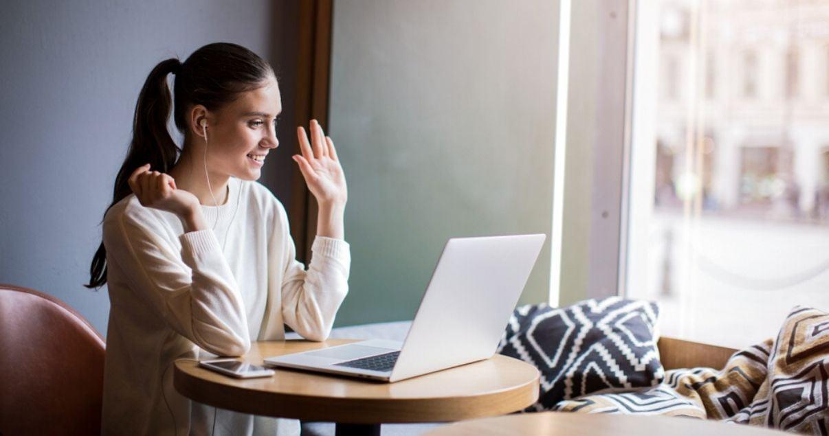 Mujer joven adulta cabello marron, peinada con una cola de caballo, ojos claros, vestida con un pulouver blanco sentada en un bar sonriendo frente a la pantalla de su laptop que tiene abierta una web para hoteles en