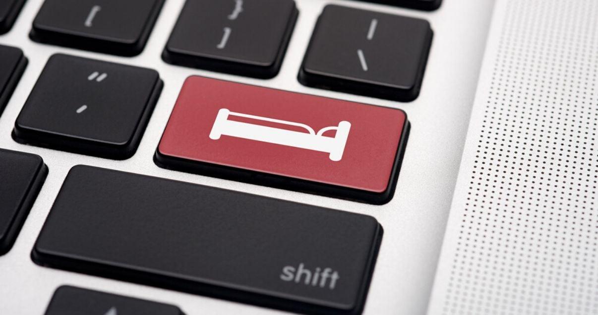 Teclado de computadora color plateado con tecas negras y una tecla roja con icono de cama para representar el impacto de las reservas de habitaciones a traves de web para hoteles