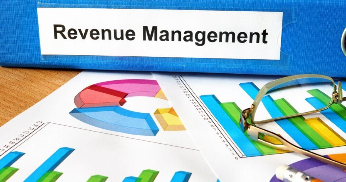 Primer plano de carpeta azul con etiqueta que dice revenue management colocada sobre escritorio de madera marron junto a reportes con graficos de barra que informan sobre los ingresos de un hotel