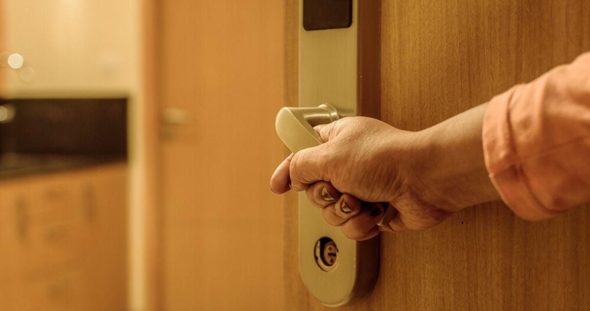 Primer plano de mano de hombre joven adulto en picaporte electrico de puerta de acceso a habitacion de un hotel que aplica revenue management