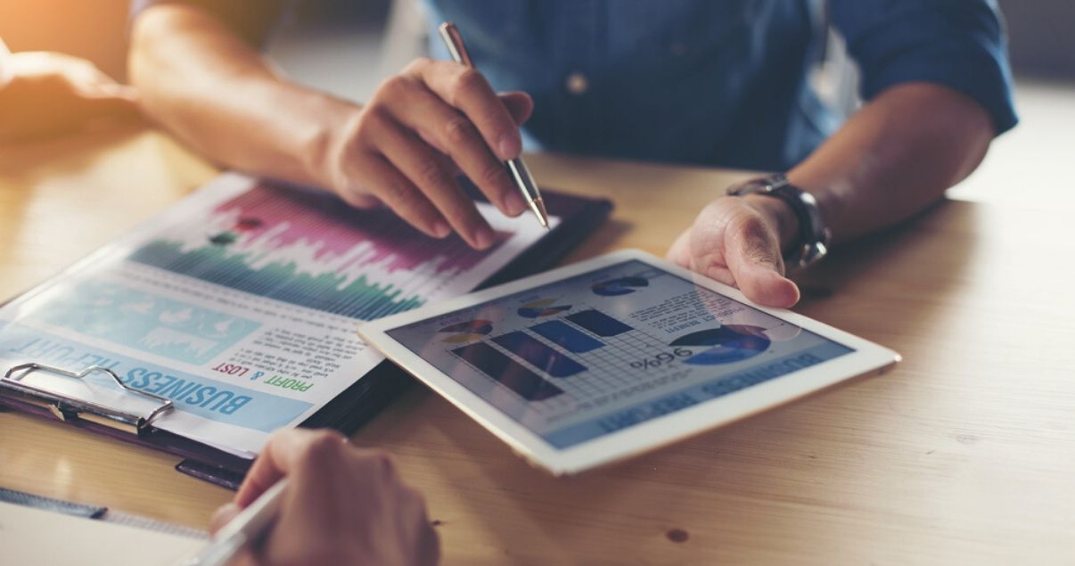 Primer plano de mano de un hombre joven adulto sobre escritorio de madera marron revisando reportes de la gestion de revenue management en el hotel en el que trabaja