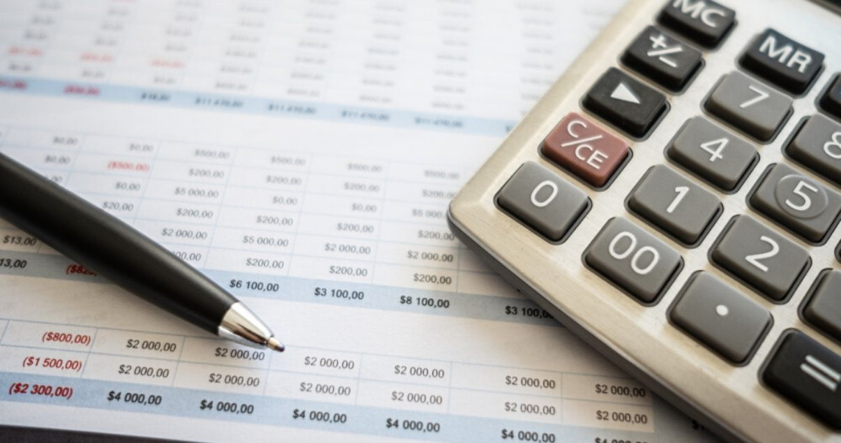 Primer plano de un reporte de numeros que arrojo una gestion de revenue management junto a una calculadora y una lapicera negra