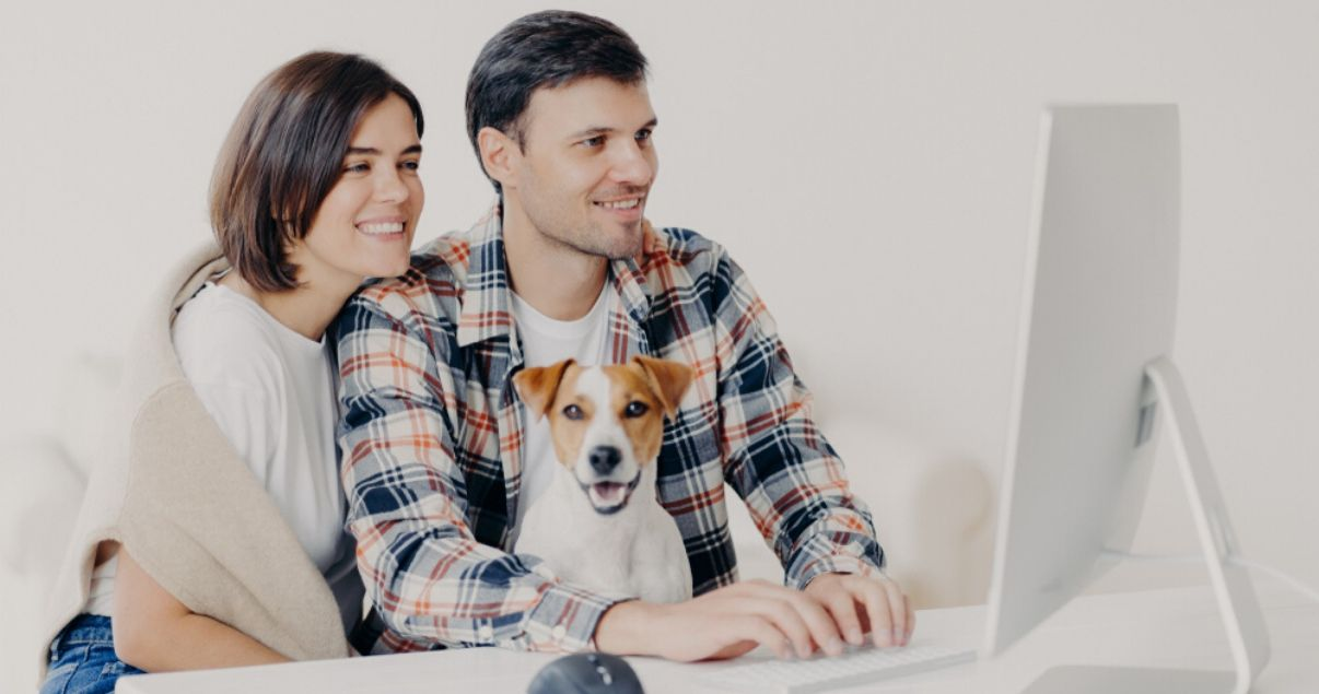 Primer plano de una pareja de hombre y mujer jovenes adultos sentados frente al monitor blanco de su computadora junto a su pequeno perro mientras dejan resenas sobre sus experiencias en hoteles pet friendly en las u
