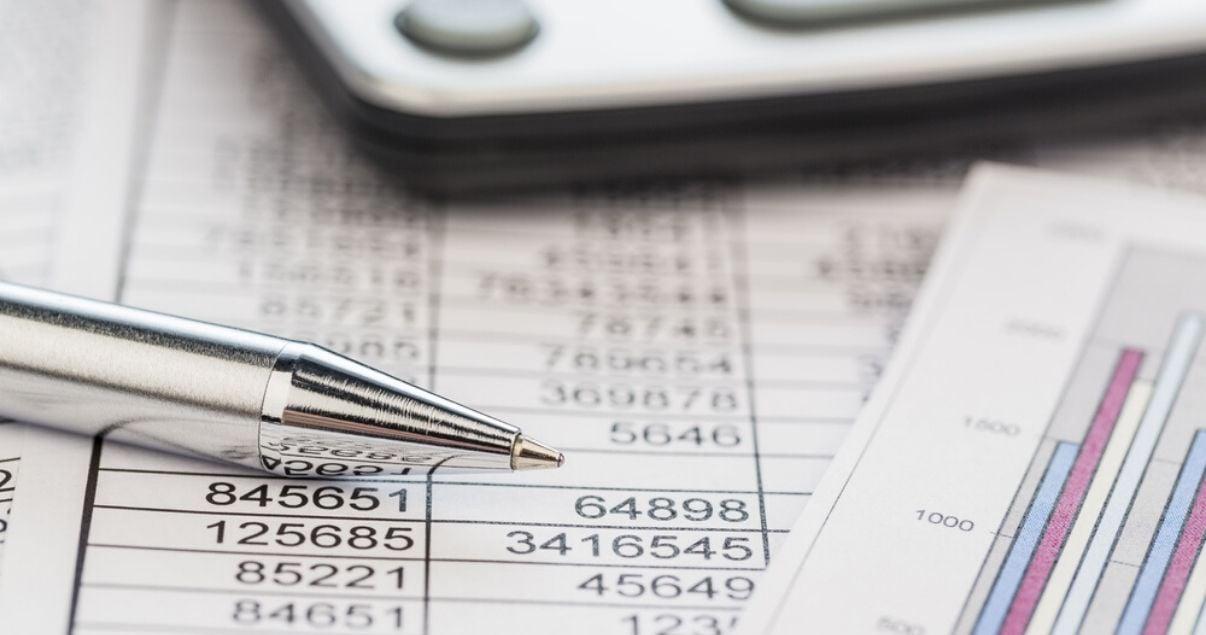 Primer plano de una pluma plateada y una calculadora sobre reportes de balance de un hotel que implementa revenue management