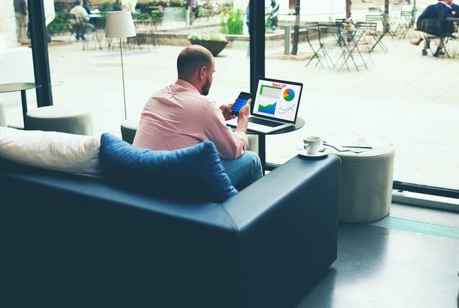 Empleado de hotel sentado en el sofa tohaciendo monitoreo de reputacion online