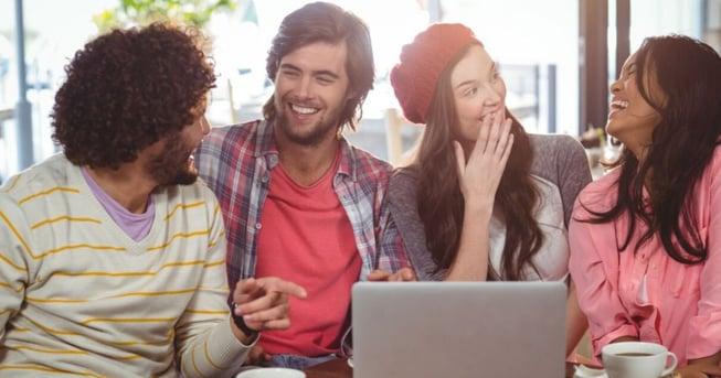 Jovenes millenials potenciales huespedes de un hotel riendo mientras hacen una reserva de habitaciones para sus proximas vacaciones