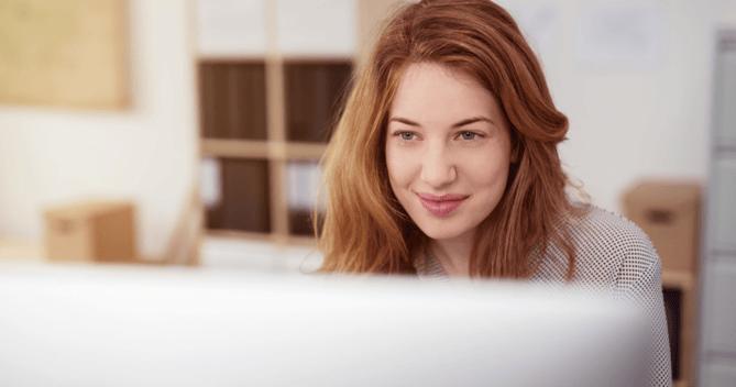 Mujer adulta trabajando en la oficina de un Hotel y sonriendo porque lee los comentarios positivos de huespedes que colaboran con la construccion de su reputacion en Internet positiva